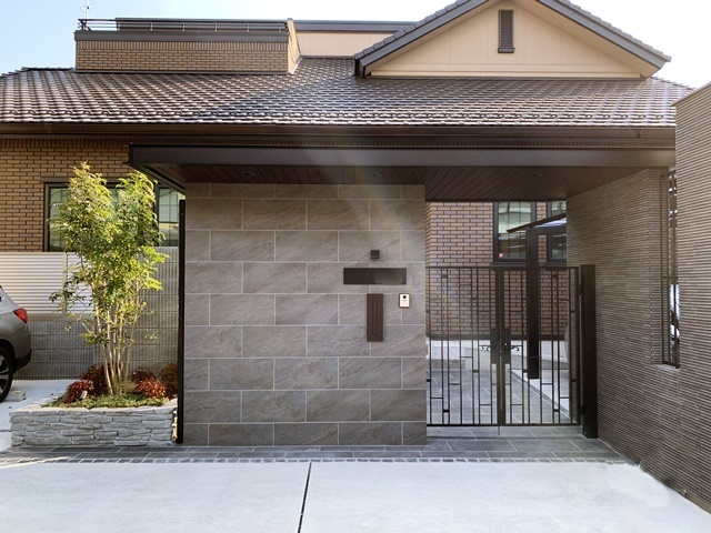 LABOT::タイル張りのシャッターと木目調の門屋根(昼間)